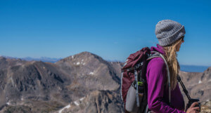 image of lady holding her camera high up in mountain ranges, managed to hire a PA so she could go climbing