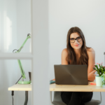 A female virtual assistant sitting at a desk with her laptop offering virtual assistant skills